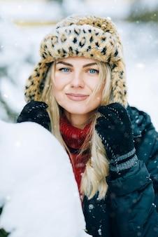 Meisje in een modieuze muts met luipaardprint verheugt zich in de sneeuw