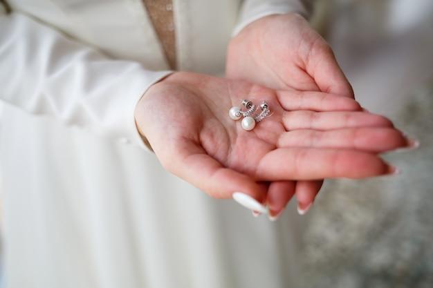 Meisje in een mooie witte jurk houdt oorbellen in haar handen