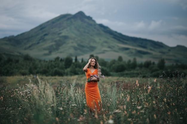 Meisje in een oranje jurk met een boeket bloemen wandelen langs het veld