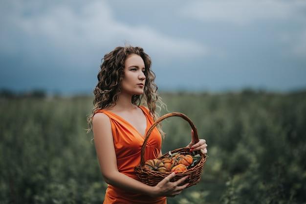 Meisje in een oranje jurk met een mand die langs het veld loopt