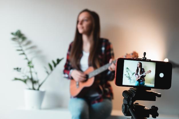Meisje in een overhemd en spijkerbroek schrijft een vlog aan de telefoon over het spelen van ukelele.