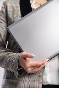 Meisje in een pak heeft een grijze laptop in haar handen.