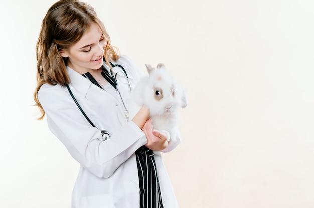 Meisje in een pak van een arts een dierenarts met een konijn in haar handen
