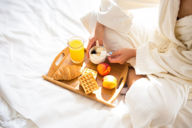 Meisje in een peignoir die ontbijt in bed eet