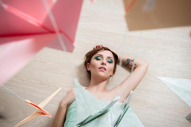 Meisje in een pistachekleurige jurk droomt op het achtergrondpapier van vogels. origami kraanvogels, draken. romantisch delicaat beeld van een meisje