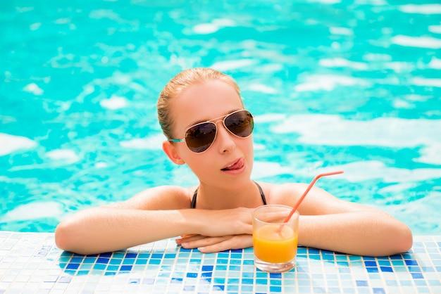 Meisje in een pool met sap en glazen die tong tonen
