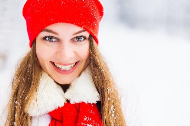 Meisje in een rode hoed glimlachend op koude winterdag