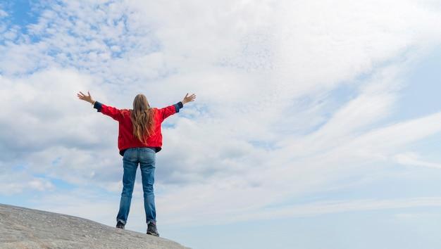 Meisje in een rode jas met opgeheven armen staat op een enorme kei. witte wolken in de blauwe lucht. kopieer ruimte.