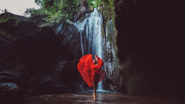 Meisje in een rode jurk dansen in een waterval. Gratis Foto