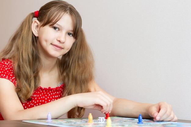 Meisje in een rode jurk een bordspel spelen