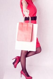 Meisje in een rode jurk en hoge hakken houdt pakketten in haar hand