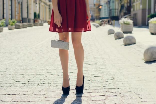 Meisje in een rode jurk en zwarte highheels met koppeling in handen straat achtergrond