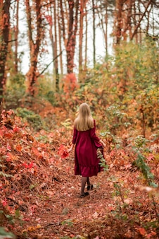 Meisje in een rode jurk in het herfstbos. een prachtig sprookjesbos. foto van de achterkant.