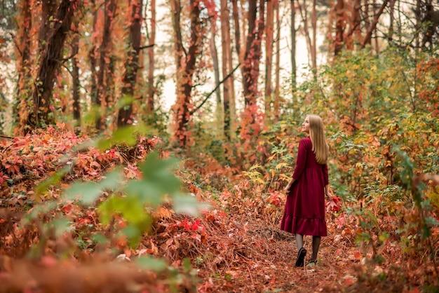 Meisje in een rode jurk loopt in het herfstbos. prachtig sprookjesbos