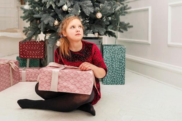 Meisje in een rode jurk met dozen vol cadeaus en kijkt dromerig weg