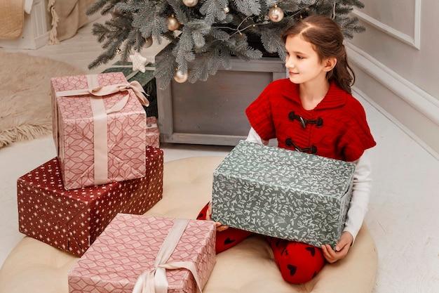 Meisje in een rode jurk met dozen vol cadeaus