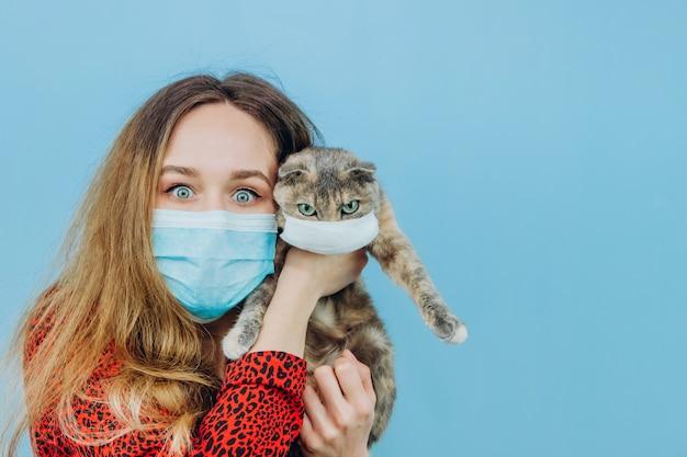 Meisje in een rode jurk met een medisch masker op haar gezicht houdt een kat.