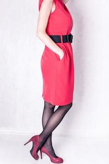 Meisje in een rode jurk met zwarte riem en hoge hakken op een witte achtergrond