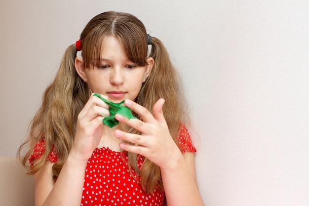 Meisje in een rode jurk spelen met een groen slijm