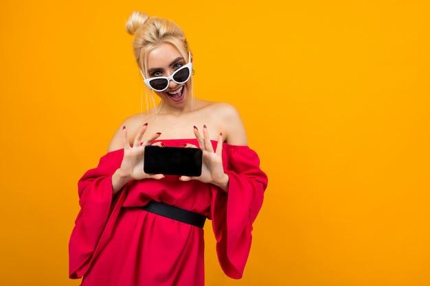 Meisje in een rode jurk toont een leeg telefoonscherm op een gele achtergrond