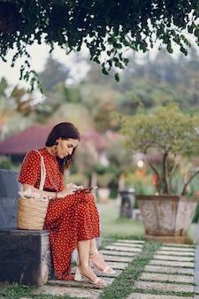 Meisje in een rode jurk zitten en gebruik de telefoon