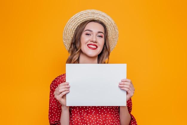 Meisje in een rode kleding die en een a4 affiche glimlacht houdt die over oranje achtergrond wordt geïsoleerd