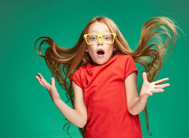 Meisje in een rode t-shirt met losse haren emoties gele glazen groene achtergrond