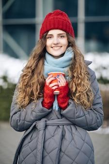 Meisje in een rode warme muts met een kopje koffie in haar handen staat in de winter op straat.