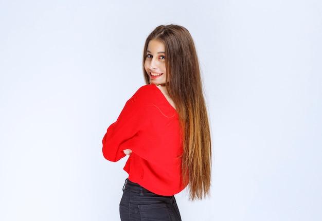 Meisje in een rood shirt dat de armen kruist en poses uit het profiel geeft.