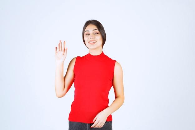 Meisje in een rood shirt dat de hand opsteekt en naar boven wijst.