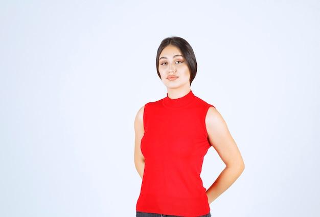 Meisje in een rood shirt dat positieve en verleidelijke poses geeft.