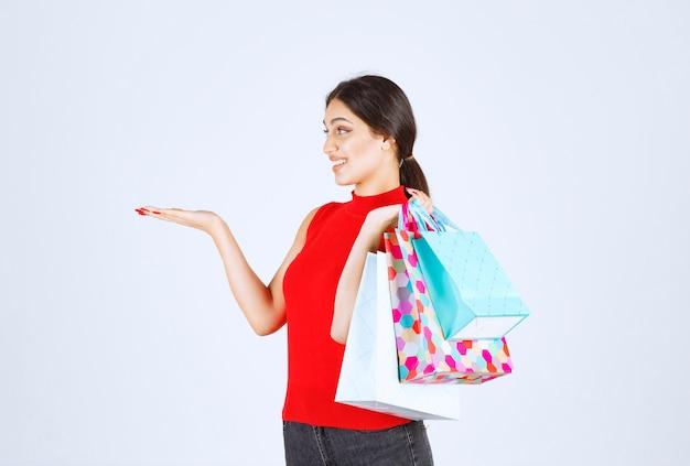 Meisje in een rood shirt met kleurrijke boodschappentassen.