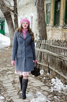 Meisje in een roze baret en een grijsblauwe jas gaat langs de straat van de oude stad