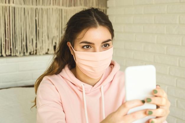 Meisje in een roze masker ter bescherming tegen 2019-ncov covid-19 thuis in sociaal isolement.