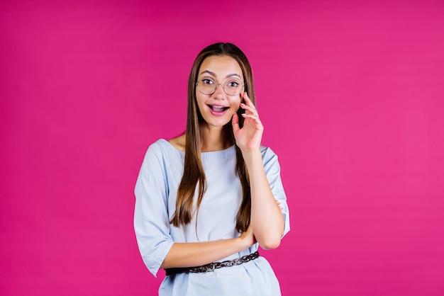 Meisje in een roze studio met een uitdrukking van nieuwsgierigheid in haar gezicht kijkt door een bril naar visie