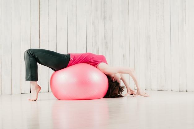 Meisje in een roze top, het maken van een brug over een roze fitball in een sportschool