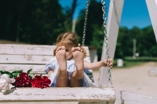 Meisje in een schommelbank met bloemen
