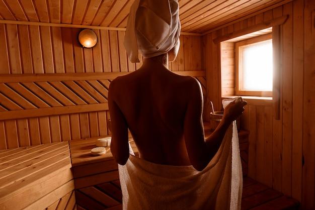 Meisje in een spa-behandeling in een traditionele sauna met een borstel voor de huid en een washandje.