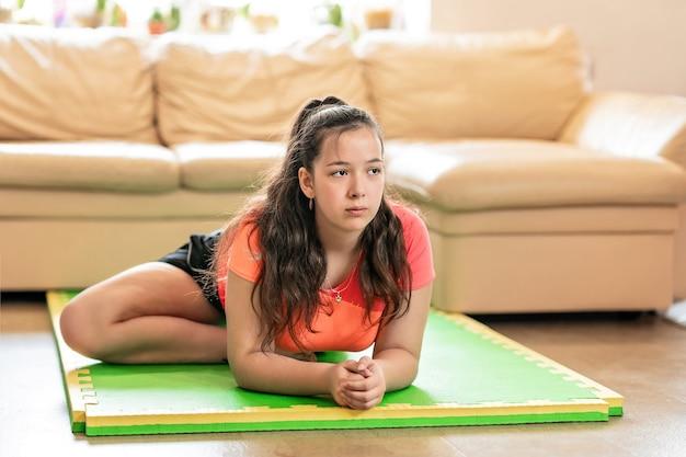 Meisje in een sportuniform zit op een mat en doet stretching, blijf thuis en een gezond levensstijlconcept