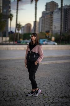 Meisje in een stad op een winterse middag. meisje gekleed in stedelijke kleding.