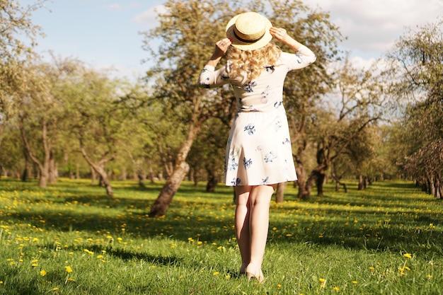 Meisje in een strohoed in de tuin. achteraanzicht. trendy casual zomer- of lente-outfit