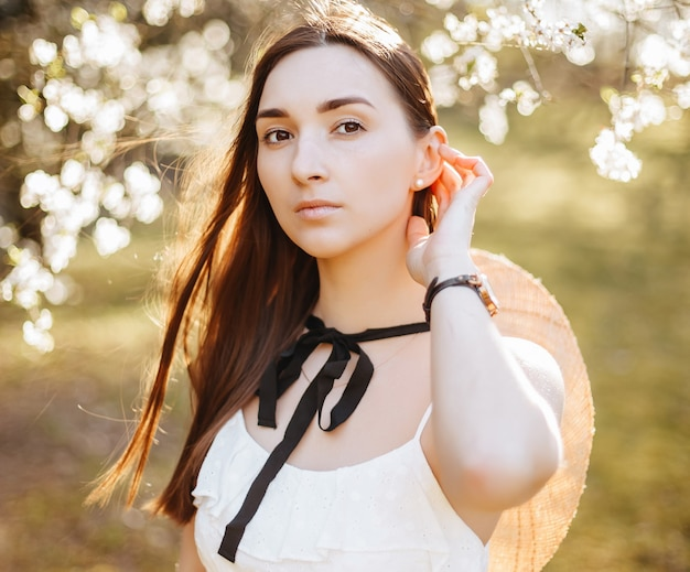 Meisje in een strooien hoed in het voorjaar in het park. brunette met lang haar houdt een hoed op een achtergrond van de zomerse natuur. jeugd en schoonheid.