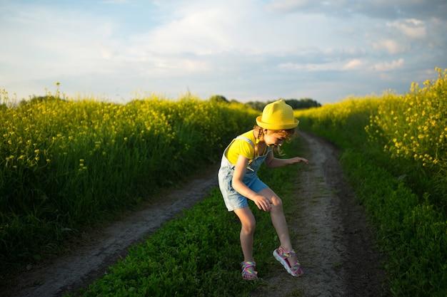 Meisje in een veld doodt muggen die haar handen en voeten bijten. het kind slaat zichzelf op het lichaam, bescherming tegen insectenbeten, afweermiddel veilig voor kinderen. buitenrecreatie, tegen allergieën Premium Foto
