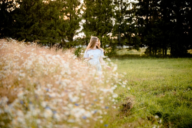 Meisje in een veld in de ondergaande zon met madeliefjes