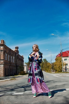 Meisje in een vintage etnische mode handgemaakte jurk poseren buitenshuis. ongebruikelijk retro kostuum op het meisjeslichaam, glimlach en vrolijke emoties. rusland, sverdlovsk, 10 juni 2019