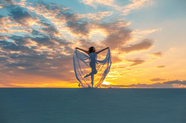 Meisje in een vlieg witte jurk danst en vormt in de zandwoestijn bij zonsondergang