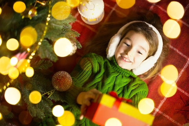 Meisje in een warme gebreide trui en bontkoptelefoon ligt op een deken bij de kerstboom met een geschenkdoos. kerstavond, een droom en een wens. nieuwjaar, feestelijke sfeer, slingers en bokeh
