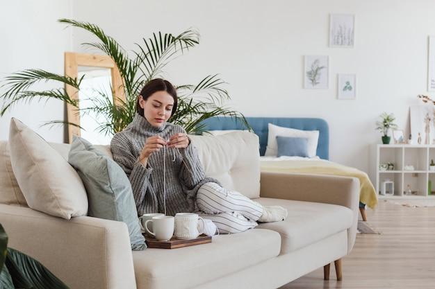 Meisje in een warme grijze trui breit zittend op een bank in een gezellig interieur hygge