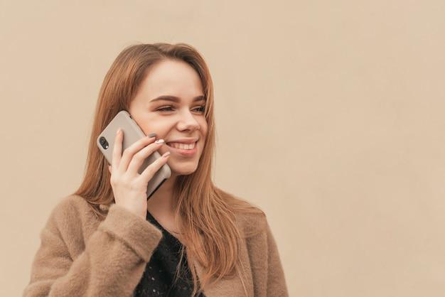 Meisje in een warme jas, staande op de achtergrond van een beige muur, praten aan de telefoon en glimlachen