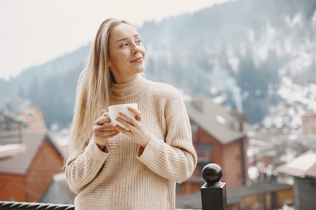 Meisje in een warme lichte jas. vakantie in de bergen. dame met lang haar.